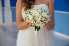 Beautiful wedding bouquet in hands of the bride. Gold ring and white dress Stock Images