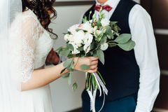 Beautiful wedding bouquet in hands of the bride. Near groom Royalty Free Stock Photo