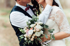 Beautiful wedding bouquet in hands of the bride. Near groom Stock Images