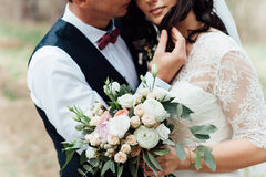 Beautiful wedding bouquet in hands of the bride. Near groom Royalty Free Stock Photography