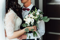 Beautiful wedding bouquet in hands of the bride. Near groom Stock Photos