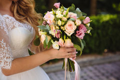 Beautiful wedding bouquet in hands of the bride. Part  white dress Royalty Free Stock Photo