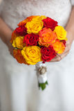 Beautiful wedding a bouquet in hands of the bride. Bouquet of red, orange and yellow roses in bride's hands Stock Photos