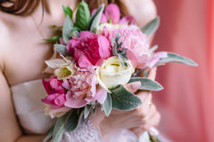 Beautiful wedding bouquet in hands of the bride. Selective focus Royalty Free Stock Image