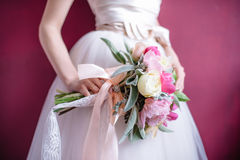 Beautiful wedding bouquet in hands of the bride. Selective focus Stock Photos