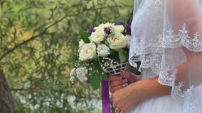 Wedding bouquet in hands. A beautiful wedding bouquet in the hands of a young bride dressed in a white wedding dress. A large bouquet of fresh white roses and stock video footage