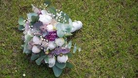 Beautiful wedding bouquet lies on the grass.  stock footage