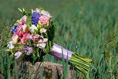 Beautiful wedding bouquet lies on the stump in the tall grass royalty free stock image