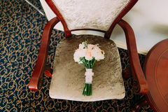 Beautiful wedding bouquet lies on vintage beige chair.  Bouquet consists of pink and white roses Royalty Free Stock Images