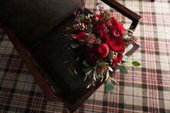 Beautiful wedding bouquet on a luxurious leather chair, against a striped carpet, close-up. Bouquet of red roses and other flowers stock photography