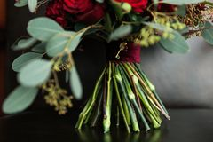 Beautiful wedding bouquet on a luxurious leather chair, close-up. Bouquet of red roses and other flowers, green leaves and buds, stock photography