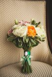 Beautiful wedding bouquet on a luxurious velour chair, close-up. Bouquet of different flowers and green leaves, tied with satin. Ribbon, blurred background stock image