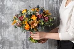 Beautiful wedding bouquet of mixed flowers in woman hand. the work of the florist at a flower shop. Beautiful bouquet of mixed flowers into a vase on wooden royalty free stock photo