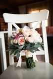 Beautiful wedding bouquet on a new light colored wooden chair, close-up. Bridal bouquet of different colors and green leaves, tied stock photo