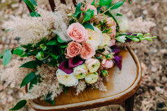 Beautiful wedding bouquet on an old brown chair standing outside in park. Stock Photo