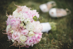 Beautiful wedding bouquet and a pair of white shoes. Beautiful  wedding bouquet and a pair of white shoes laying on the green lawn Stock Photography