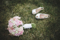 Beautiful  wedding bouquet and a pair of white shoes laying on t. He green lawn Stock Photo
