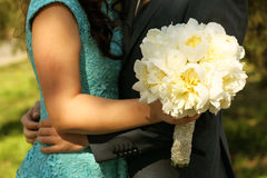 Beautiful wedding bouquet with peonies and a lovely couple Stock Photo