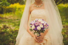 Beautiful wedding bouquet. With purple flowers in the hands of the bride Royalty Free Stock Images