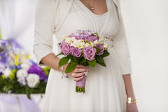 Beautiful wedding bouquet of purple roses in the hands Stock Photography