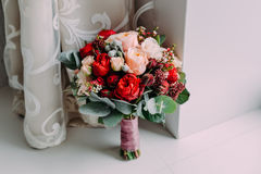 Beautiful wedding bouquet of red flowers, pink flowers and greenery stand next to the window Stock Photo