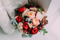 Beautiful wedding bouquet of red flowers, pink flowers and greenery stand next to the window Stock Image