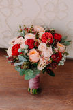 Beautiful wedding bouquet of red flowers, pink flowers and greenery stand on the wall background Royalty Free Stock Images