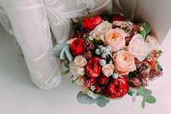 Beautiful wedding bouquet of red flowers, pink flowers and greenery stand next to the window Royalty Free Stock Photo