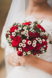 Beautiful wedding bouquet of red roses flowers in hands of anony Stock Photo