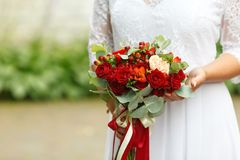 Beautiful wedding bouquet of red roses and red Hypericum berries in hands of bride. Soft focus, selective focus Royalty Free Stock Photo