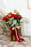 Beautiful wedding bouquet of red roses and red Hypericum berries on the sofa in the interior. Soft focus, selective focus Stock Photography
