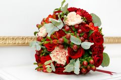 Beautiful wedding bouquet of red roses and red Hypericum berries in the white interior. Beautiful wedding bouquet of red roses and red Hypericum berries in the Stock Photography