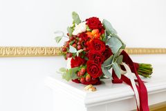 Beautiful wedding bouquet of red roses and gold wedding rings in the white interior. Beautiful wedding bouquet of red roses and red Hypericum berriesand and Stock Photo