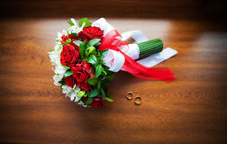 Beautiful wedding bouquet and rings on wood Royalty Free Stock Photography