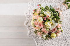 Beautiful wedding bouquet of roses and freesia with lace on white wooden background, background for valentines or wedding day Stock Photos