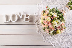 Beautiful wedding bouquet of roses and freesia with letters on white wooden background, background for valentines or wedding day Royalty Free Stock Photo