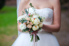 Beautiful wedding bouquet of roses in hands of Stock Images