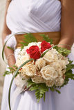 Beautiful wedding bouquet of roses in hands of the bride Stock Photo