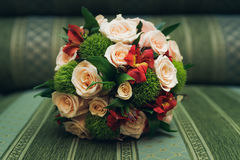 Beautiful wedding bouquet of roses lying on sofa. Beautiful wedding bouquet of roses lying on a sofa Stock Photography