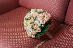 Beautiful wedding bouquet of roses lying on the sofa Stock Image