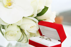 Beautiful wedding bouquet of roses and orchids and red velvet box with gold and platinum wedding rings. On glass table Royalty Free Stock Photos
