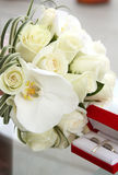 Beautiful wedding bouquet of roses and orchids and red velvet box with gold and platinum wedding rings. On glass table Stock Photo