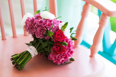 Beautiful wedding bouquet roses and peonies on pink chair Royalty Free Stock Photo