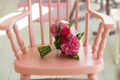 Beautiful wedding bouquet roses and peonies on pink chair Stock Image