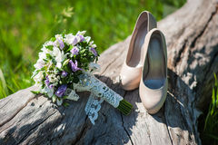 Beautiful wedding bouquet and shoes for the bride standing on a Royalty Free Stock Images