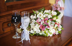 Beautiful wedding bouquet and two glasses with champagne Stock Photos