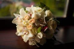 Beautiful wedding bouquet of white flowers. Lying on a dark windowsill Royalty Free Stock Photos