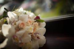 Beautiful wedding bouquet of white flowers. Lying on a dark windowsill Stock Photos