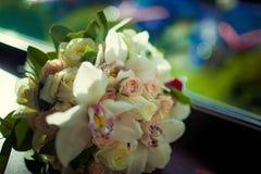 Beautiful wedding bouquet of white flowers. Lying on a dark windowsill Royalty Free Stock Image