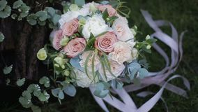 Beautiful wedding bouquet of white roses and creme carnations on the grass near an oak tree. Bride`s wedding bouquet of roses and carnations. Bouquet of stock footage
